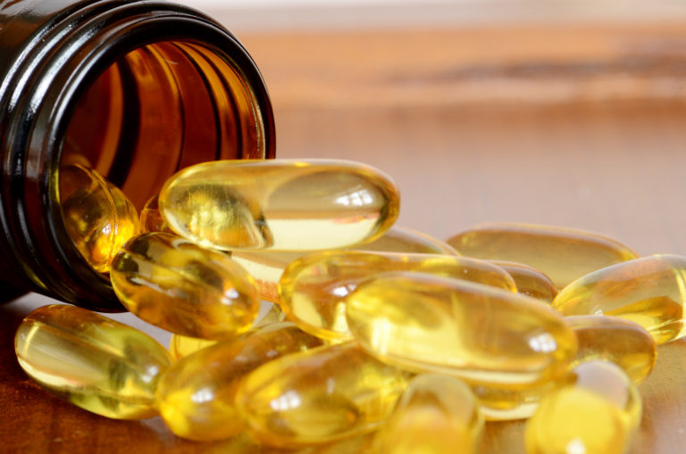 Yellow transparent capsules falling out of a brown bottle for Does fish oil help your hair grow
